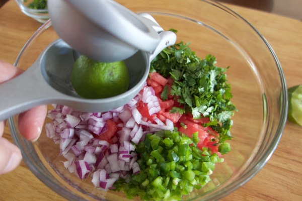 Squeezing lime into the glass mixing bowl.