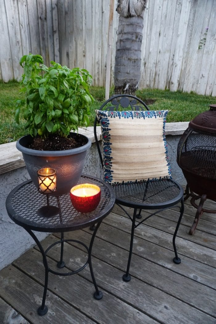 Metal Chair and side table with fun pillow and basil plant