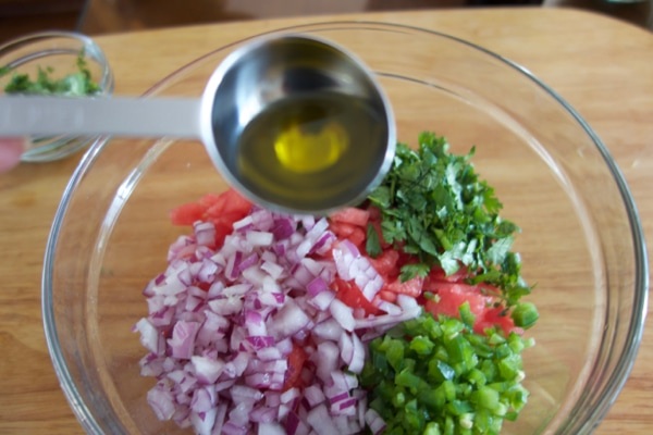 Adding a bit of olive oil to the watermelon salsa. - mommacann.com