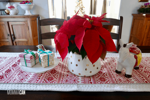 Chrismas table design with simple red poinsettias and white planter with gold polka dots. The burro steals the show and doubles as a cookie jar!